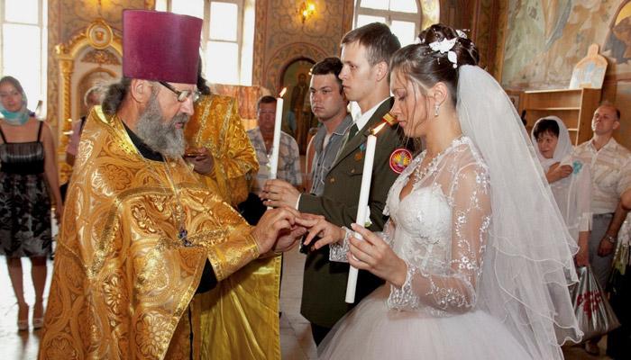 Священник одевает кольца молодым