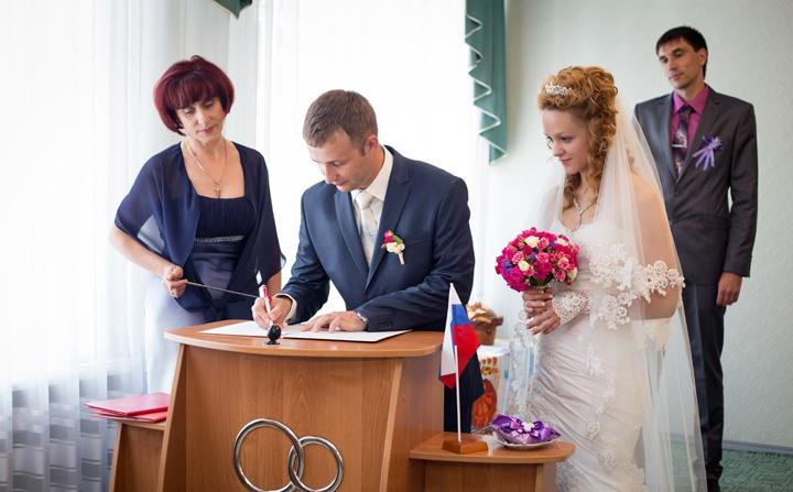 Молодой человек ставит свою роспись в книге учета браков