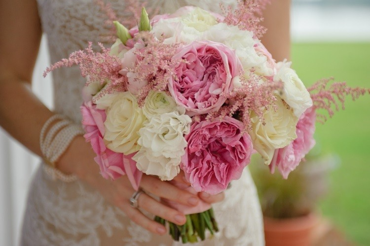 Сочетание композиции из розовых и белых цветов и белого кружевного свадебного платья